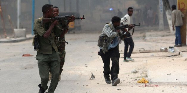 Somali government soldiers run to take their positions during gunfire after a suicide bomb attack outside...