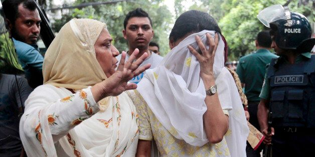 A relative tries to console Semin Rahman, covering face, whose son is missing after militants took hostages...
