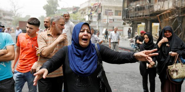 A woman reacts at the site after a suicide car bomb attack at the shopping area of Karrada, a largely...