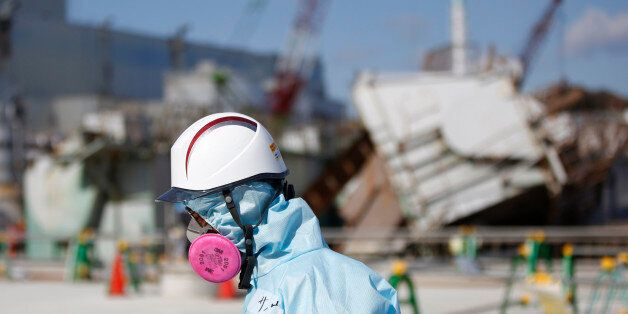 FILE - In this Feb. 10, 2016, file photo, a Tokyo Electric Power Co. (TEPCO) employee, wearing a protective...