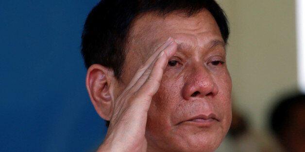 Philippines' President Rodrigo Duterte salutes during a military parade at main military Camp Aguinaldo...