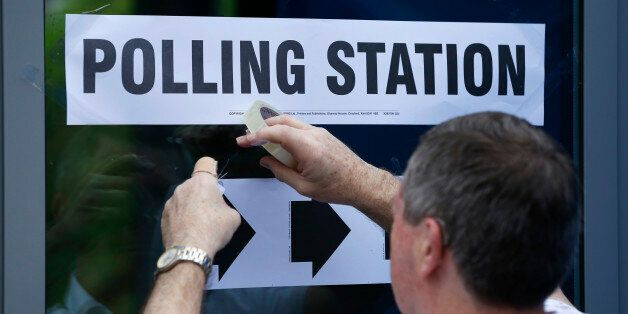 A man puts up a sign at a polling station for the Referendum on the European Union in Heald Green, Stockport,...
