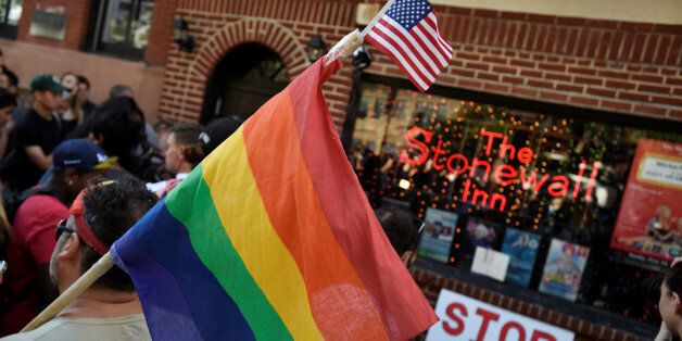 A man carries a gay pride flag at a vigil outside The Stonewall Inn on Christopher Street, considered...