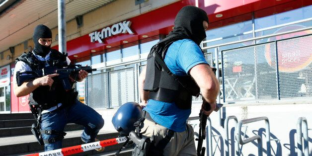 German special police walks past a cinema complex after a masked man with a gun and ammunition belt opened...