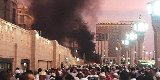 In this photo provided by Noor Punasiya, people stand by an explosion site in Medina, Saudi Arabia, Monday,...