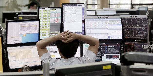 A currency trader watches monitors at the foreign exchange dealing room of the KEB Hana Bank headquarters...