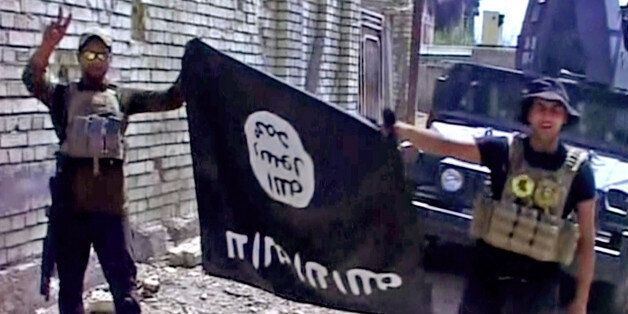 This image made from Associated Press video shows, Iraqi troops turn the Islamic State flag upside down...