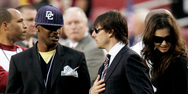 Actors Jamie Foxx (L), Tom Cruise (C) and Katie Holmes talk on the Washington Redskins sidelines before...