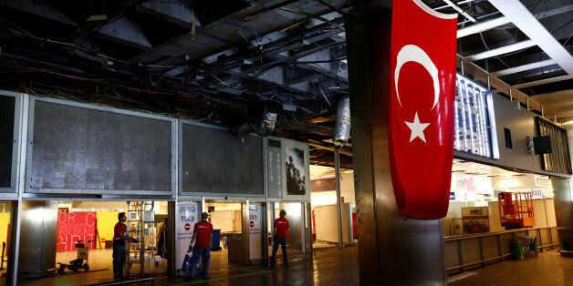 Workers repair the damaged parts of the terminal building at Turkey's largest airport, Istanbul Ataturk,...