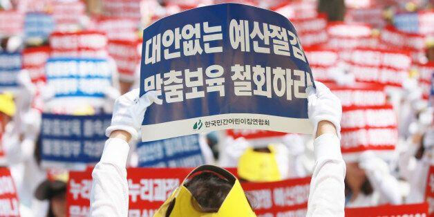 13일 서울 여의도 국회 인근에서 한국민간어린이집연합회 주최로 열린 맞춤형 보육 저지 및 누리과정예산 근본해결 촉구대회에서 참가자들이 손팻말을 흔들고