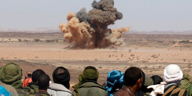 Sahrawis watch a mine explode during a demonstration organised by officials from the Saharawi Arab Democratic...