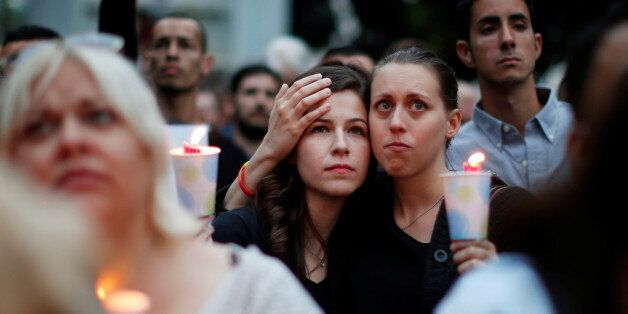 Kassandra Shore, 25, (L) and Candice Darden, 29, hold candles at a vigil in memory of victims one day...