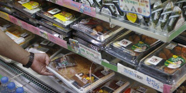 A man chooses a lunch box at a convenience store in Seoul, South Korea, August 21, 2015. South Korean...