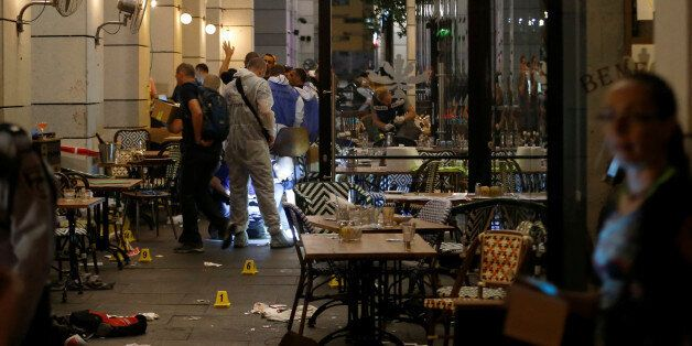Israeli policemen work inside a restaurant following a shooting attack that took place in the center...