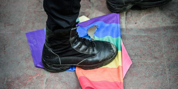A Turkish anti-riot police officer steps on a rainbow flag during a rally staged by the LGBT community...