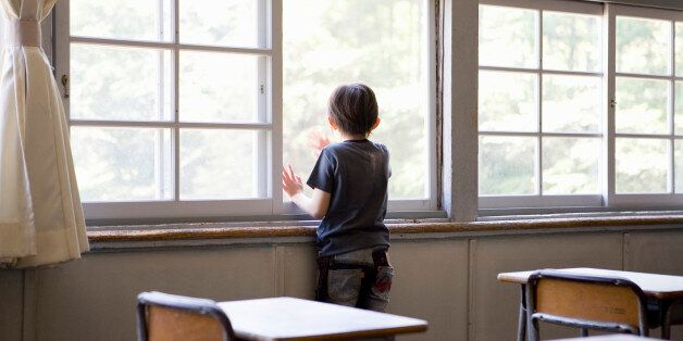 Boy (6-7) looking out of classroom window, rear