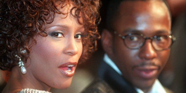 Whitney Houston looks over her shoulder as her husband Bobbi Brown looks to her at the premiere