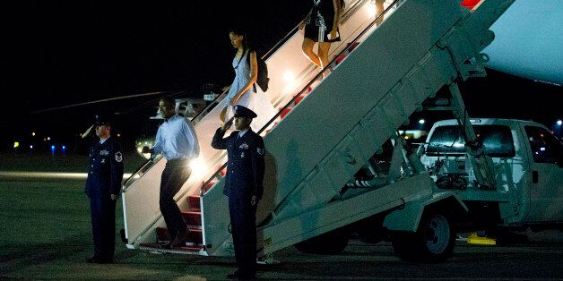 President Barack Obama, left, daughters Malia and Sasha and first lady Michelle Obama exit Air Force...