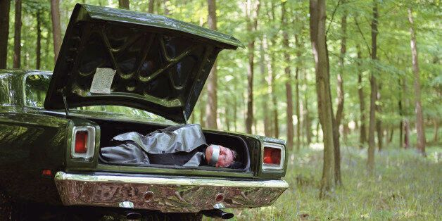 Car in woodland, mature man gagged and bound in