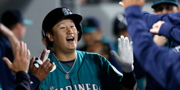 Seattle Mariners' Dae-Ho Lee is congratulated in the dugout after hitting a solo home run on a pitch...