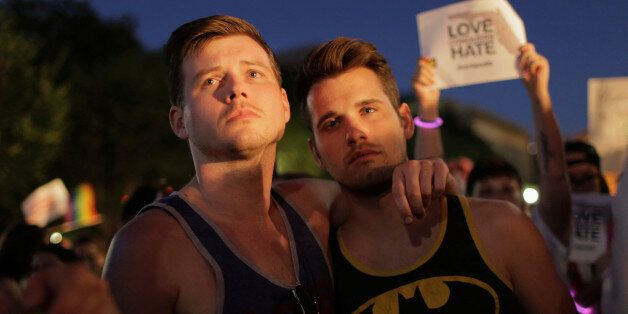 Men stand together during a vigil after the worst mass shooting in U.S. history at a gay nightclub in...