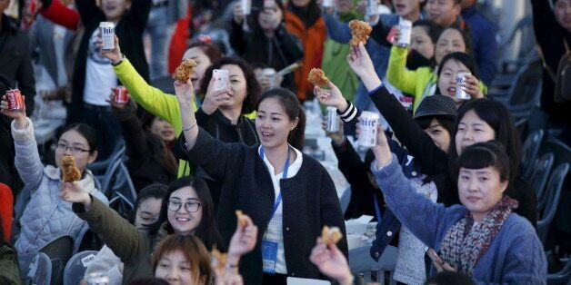 Chinese tourists make a toast with canned drinks and fried chicken pieces during an event organized by...