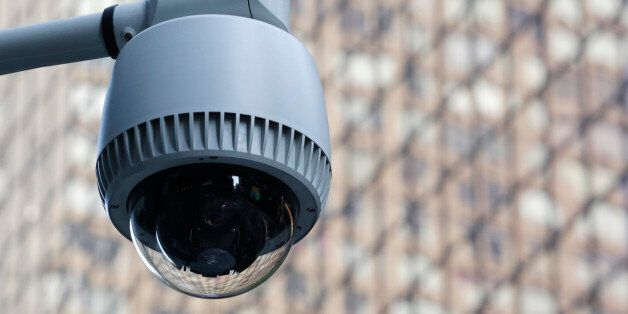 A security camera, center, is mounted on the side of a building overlooking an intersection in midtown...