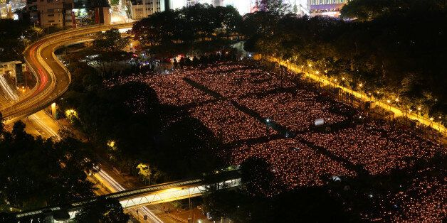 Thousands of people take park in a candlelight vigil to mark the 27th anniversary of the crackdown of...