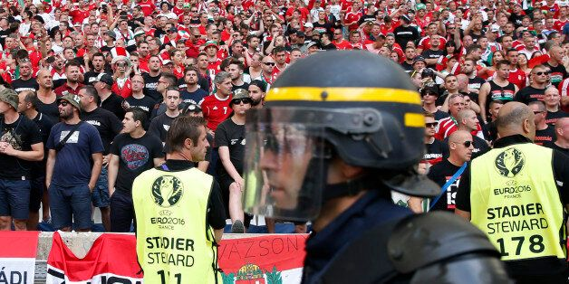 A French riot police officer walks past the Hungarian fans sector prior to the Euro 2016 Group F soccer...