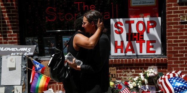 Matti Mejia (L) and Shaina Roberts embrace after laying flowers at a memorial outside The Stonewall Inn...