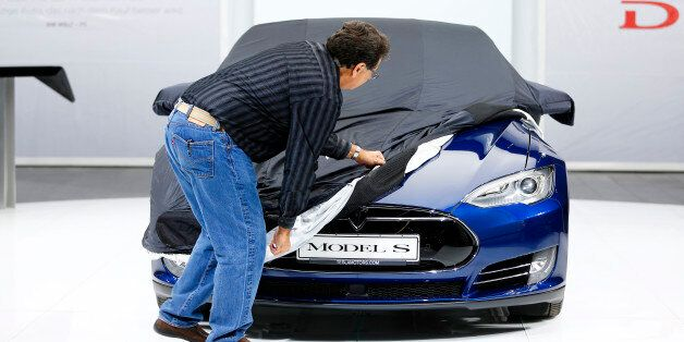 An employee covers a Tesla Model S car during the media day at the Frankfurt Motor Show (IAA) in Frankfurt,...