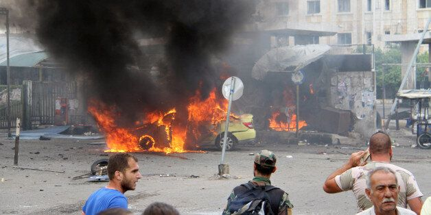 A Syrian army soldier and civilians inspect the damage after explosions hit the Syrian city of Tartous,...