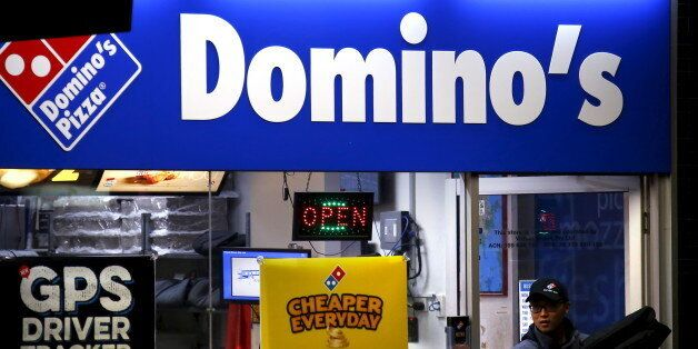 A worker carries a pizza for delivery as he exits a Domino's pizza store in Sydney, Australia, August...
