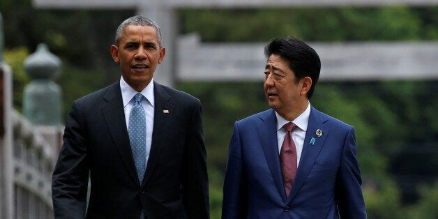U.S. President Barack Obama (R) puts his arm around Japanese Prime Minister Shinzo Abe after they laid...