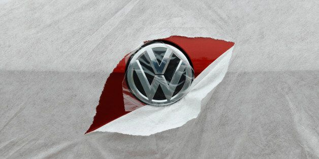 A VW badge is seen through torn wrapping as a Volkswagen Golf is delivered to a car dealership in Portslade...