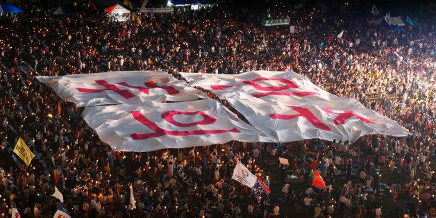 People hold a large banner, which