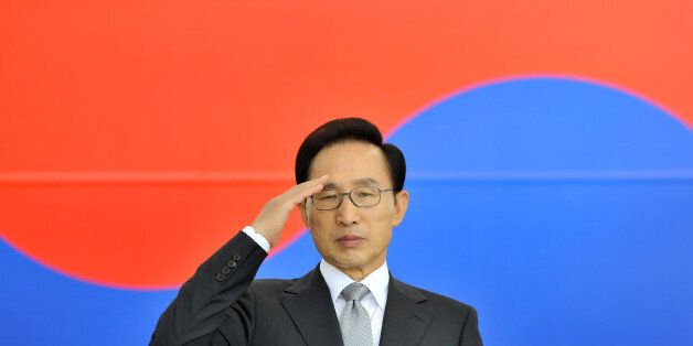 South Korean President Lee Myung-bak salutes in front of the national flag during a ceremony to mark...