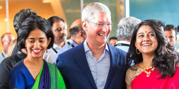 In this Handout photograph provided by Apple Media office, Apple chief Tim Cook talks with Indian colleagues...