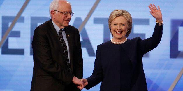 Democratic U.S. presidential candidates Senator Bernie Sanders and Hillary Clinton shake hands before...