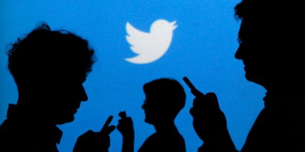 People holding mobile phones are silhouetted against a backdrop projected with the Twitter logo in this...