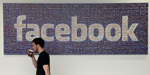 FILE - In this March 15, 2013, file photo, a Facebook employee walks past a sign at Facebook headquarters...