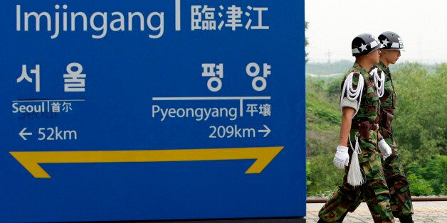 South Korean military police officers walk by a sign showing the distance to the North Korean capital...