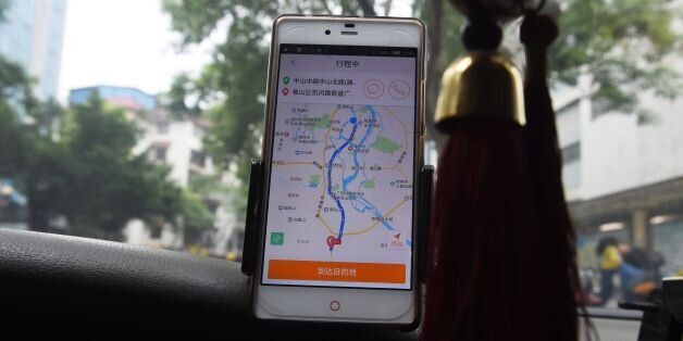A taxi driver uses the Didi Chuxing app while driving along a street in Guilin, in China's southern Guangxi...