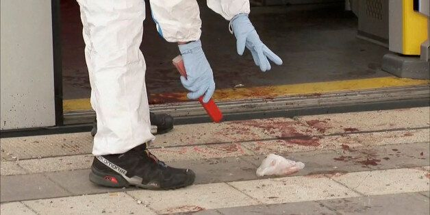 A still image taken from a video shows an official investigating the site of a knife attack at the train...