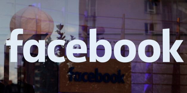 The logo of Facebook is pictured on a window at new Facebook Innovation Hub during a media tour in Berlin,...