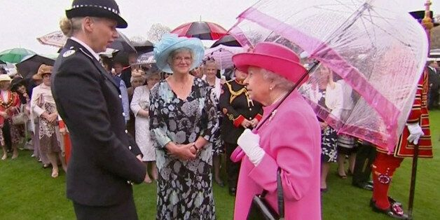 Britain's Queen Elizabeth speaks to Commander Lucy D'Orsi during a garden party at Buckingham Palace...