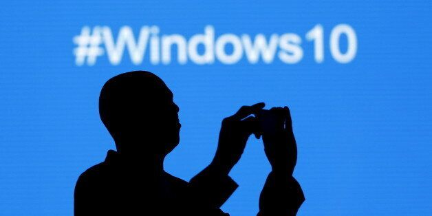 A Microsoft delegate takes a picture during the launch of the Windows 10 operating system in Kenya's...