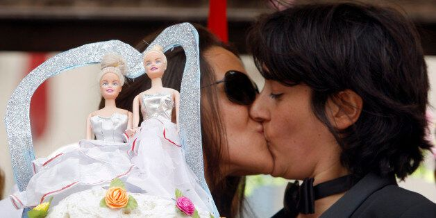 A lesbian couple kisses near a wedding cake as they take part in a gay pride parade in Rome June 7, 2008....