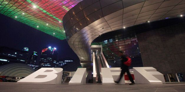 FILE - In this Wednesday, Oct. 2, 2013 file photo, a man walks in front of the venue for the Busan International...