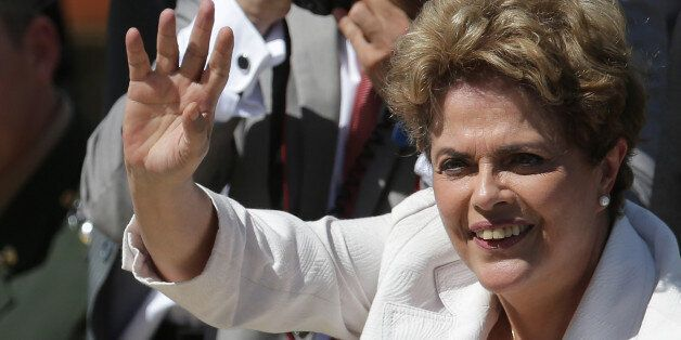 Brazilian President Dilma Rousseff greets supporters as she leaves Planalto president palace in Brasilia,...